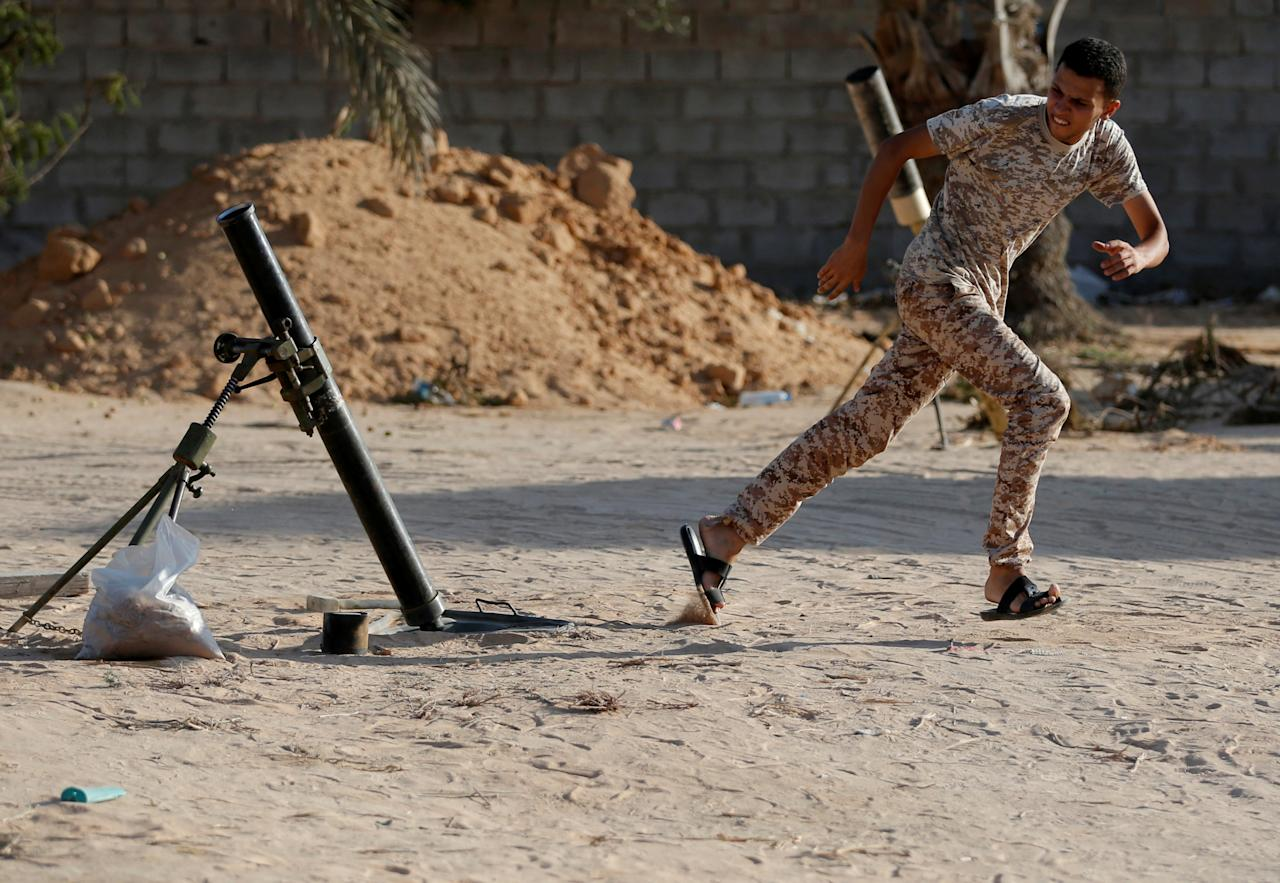 A fighter of Libyan forces allied with the U.N.-backed government fires a 81 mm mortar round in Sirte, Libya, July 26, 2016. REUTERS/Goran Tomasevic