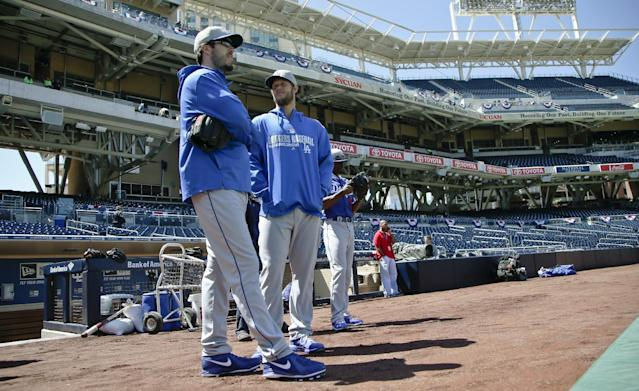 Los Angeles Dodgers starting pitcher Clayton Kershaw, right, who the Dodgers placed on the disabled list last week, talks fellow pitcher Dan Haren prior to a baseball game Tuesday, April 1, 2014, in San Diego. (AP Photo/Lenny Ignelzi)