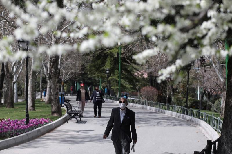 FILE PHOTO: A man wears a protective face mask, amid fear of coronavirus disease (COVID-19), as he walks at Mellat park, ahead of the Iranian New Year Nowruz, March 20, in Tehran