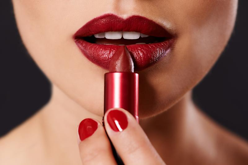 Closeup image of a woman applying lipstick