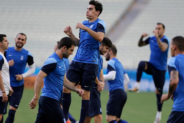 Greece's Lazaros Christodoulopoulos, center top, jump ups during an official training session the day before the group C World Cup soccer match between Greece and Ivory Coast at the Arena Castelao in Fortaleza, Brazil, Monday, June 23, 2014. (AP Photo/Fernando Llano)