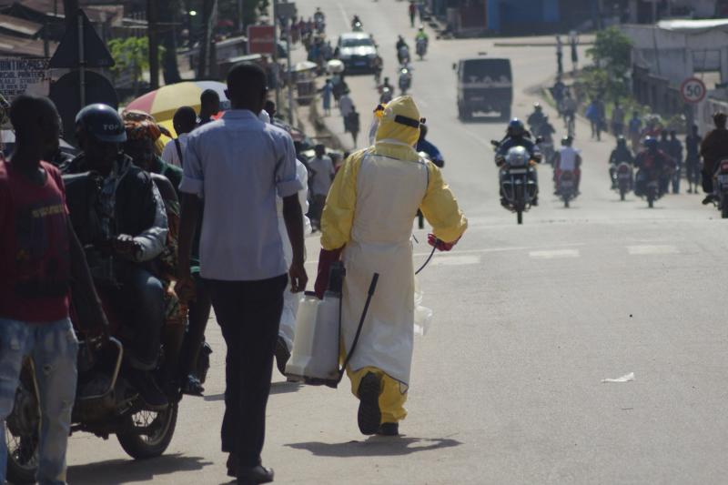 A health worker with disinfectant spray walks down a street outside the government hospital in Kenema, July 10, 2014. Ebola has killed 632 people across Guinea, Liberia and Sierra Leone since an outbreak began in February, putting strain on a string of weak health systems facing one of the world's deadliest diseases despite waves of international help. Picture taken July10, 2014. REUTERS/Tommy Trenchard (SIERRA LEONE - Tags: HEALTH)