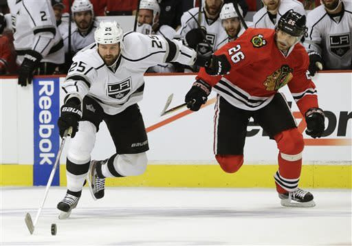 Los Angeles Kings left wing Dustin Penner (25) maintains control of the puck against Chicago Blackhawks center Michal Handzus (26) during the first period of Game 1 of the NHL hockey Stanley Cup Western Conference finals, Saturday, June 1, 2013, in Chicago. (AP Photo/Nam Y. Huh)