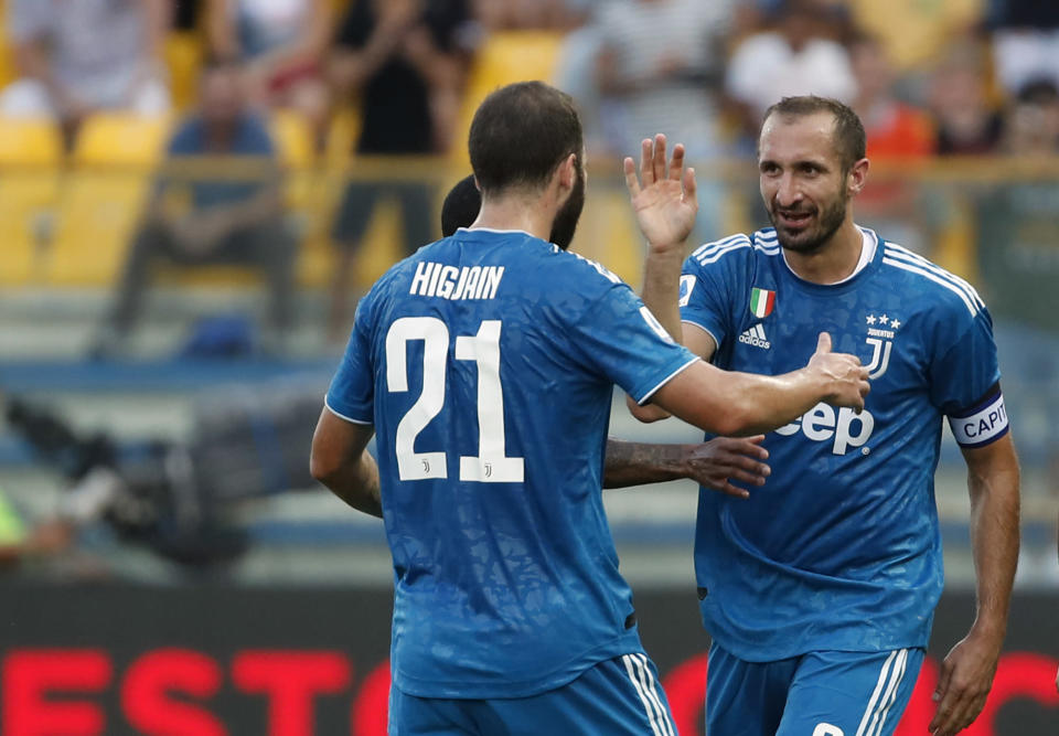 Juventus' Giorgio Chiellini, right, celebrates with teammates after scoring his side's opening goal during the Serie A soccer match between Parma and Juventus at the Tardini stadium, in Parma, Italy, Saturday, Aug. 24, 2019. (AP Photo/Antonio Calanni)