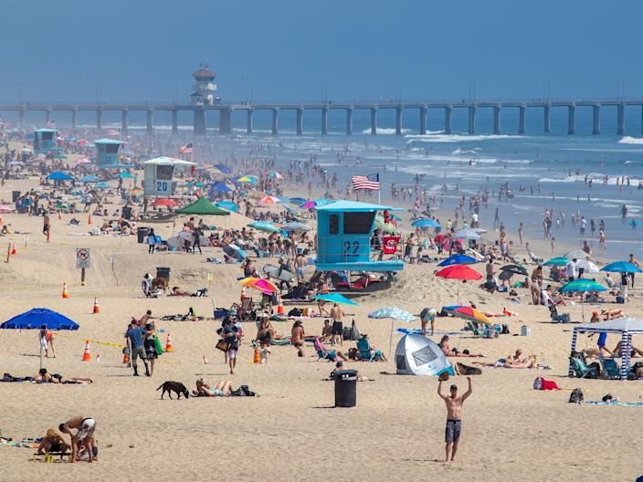 Thousands enjoy a warm, sunny day at the beach amid state-mandated stay-at-home and social distancing orders to stave off the coronavirus pandemic in Huntington Beach, California, on April 25, 2020.