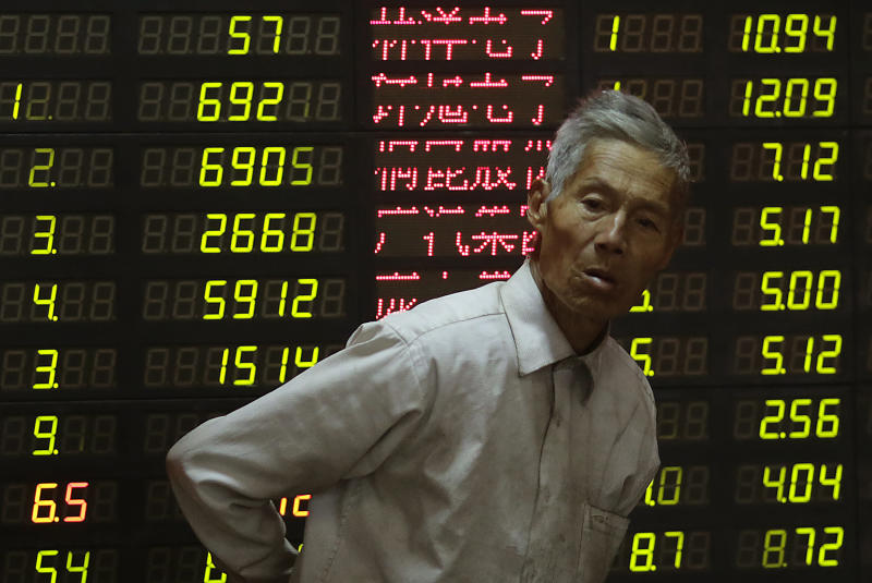 An investor looks at the stock price monitor at a private securities company in Shanghai, China, Thursday, Nov. 8, 2012. Asian stock markets tumbled Thursday after a ratings agency threatened to downgrade the U.S. if a solution to the so-called fiscal cliff isn't negotiated among lawmakers and newly re-elected President Barack Obama. Also being watched by investors is Thursday's opening of China's Communist Party congress — the once-in-a-decade forum to name China's top leadership. (AP Photo/Eugene Hoshiko)