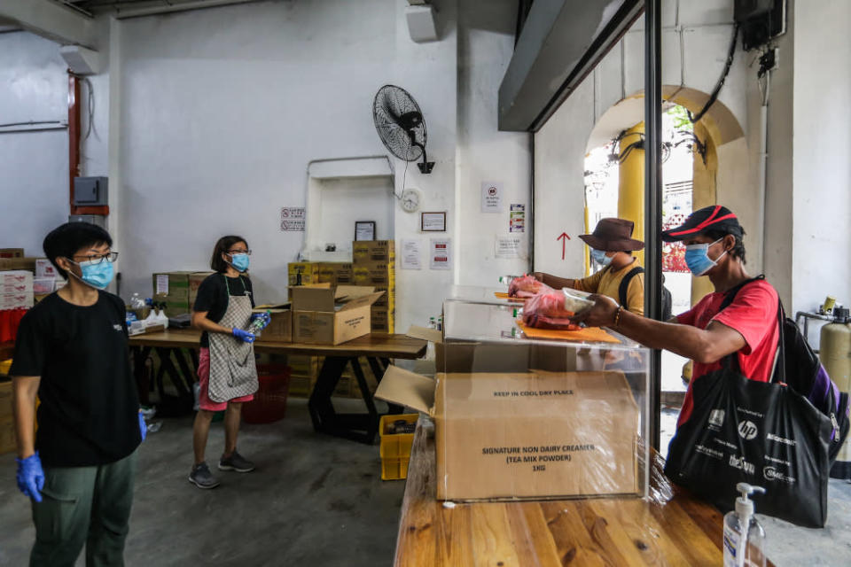 Pit Stop Community Cafe staff observe social distancing guidelines as they serve the homeless one final time in Kuala Lumpur March 30, 2020. — Picture by Firdaus Latif