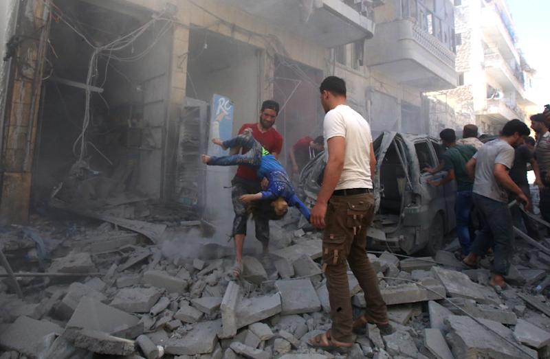 A man evacuates a young casualty following a reported air strike by regime forces and their allies in the jihadist-held Syrian town of Maaret Al-Numan in Idlib province on Sunday