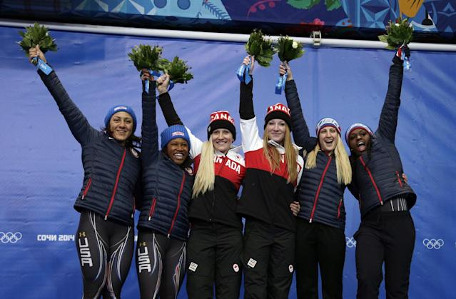 From left to right, silver medal winners from the United States Elana Meyers and Lauryn Williams, gold medal winners from Canada Kaillie Humphries and Heather Moyse, and bronze medal winners from the United States Jamie Greubel and Aja Evans pose during the flower ceremony during the women's bobsled competition at the 2014 Winter Olympics, Wednesday, Feb. 19, 2014, in Krasnaya Polyana, Russia. (AP Photo/Michael Sohn)