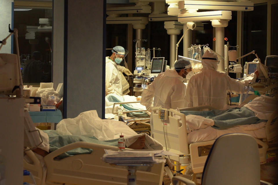 Medical personnel attend patients at Casalpalocco Covid 3 hospital in the outskirts of Rome, during the new year night, Friday, Jan. 1, 2021. At the Casalpalocco Covid 3 Hospital doctors and nurses barely seemed to register the new year as they tended to 100 patients struggling with serious to critical illness as a result of coronavirus infections. (AP Photo/Andrea Rosa)