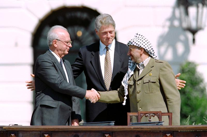 A picture taken on September 13, 1993 shows US President Bill Clinton (C) standing between PLO leader Yasser Arafat (R) and Israeli Prime Minister Yitzahk Rabin (L) as they shake hands for the first time, at the White House in Washington DC (AFP Photo/J. David Ake)