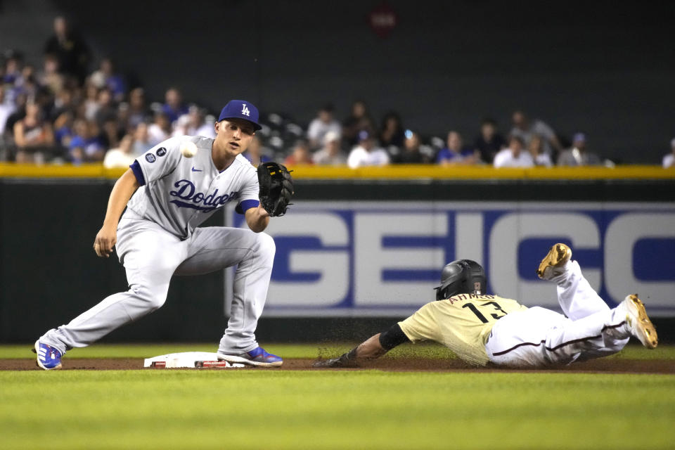 Arizona Diamondbacks' Nick Ahmed (13) steals second base under the tag by Los Angeles Dodgers shortstop Corey Seager during the fourth inning of baseball game Friday, July 30, 2021, in Phoenix. (AP Photo/Rick Scuteri)