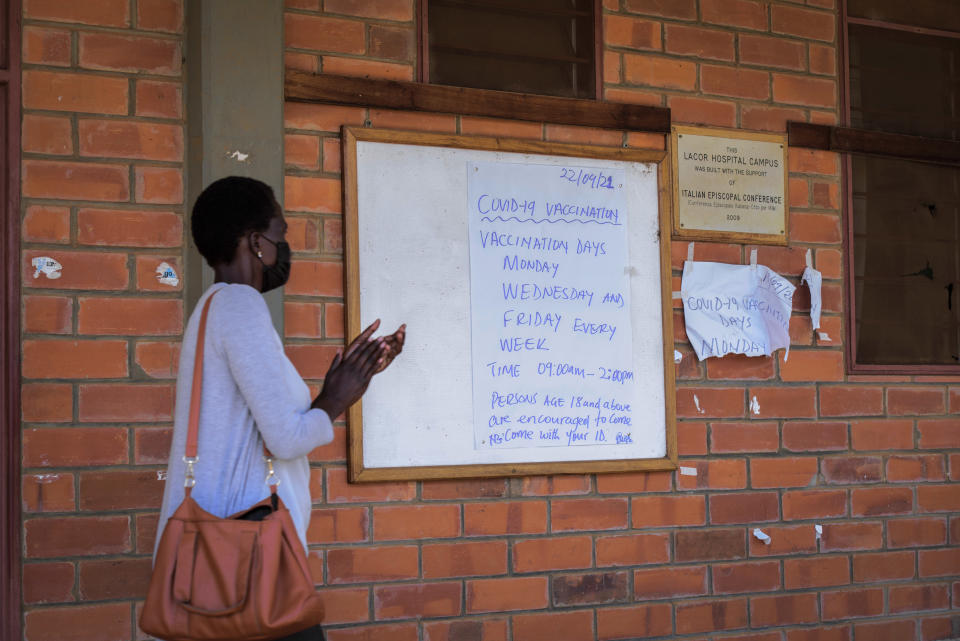 A woman walks past a board showing the coronavirus vaccine administering schedule at St. Mary's Hospital Lacor in Gulu, Uganda Wednesday, Sept. 22, 2021. Repeated and sudden power failures plague the vaccine storage unit, adding to the logistical challenges facing efforts to ramp up vaccination across the country. (AP Photo/Nicholas Bamulanzeki)
