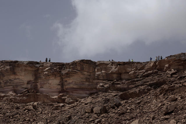 In this March 30, 2019 photo, tourists stop to look at the view on a trek led by Beduin women, in the mountains, near Wadi Sahw, Abu Zenima, in South Sinai, Egypt. Four Bedouin women are for the first time leading tours in Egypt's Sinai Peninsula, breaking new ground in their deeply conservative community, where women almost never work outside the home or interact with outsiders. They are part of Sinai Trail, a unique project in which local Bedouin tribes came together aiming to develop their own tourism. (AP Photo/Nariman El-Mofty)