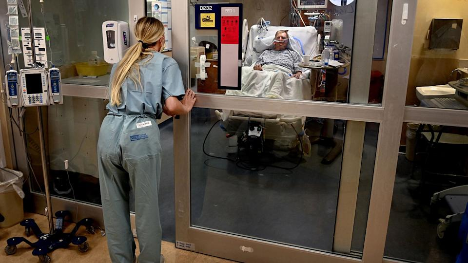 Paige Thompson, a registered nurse, checks in on a patient, Rodney Hopp, in the COVID-19 ward at Tampa General Hospital in Tampa, Fla. in August last year.