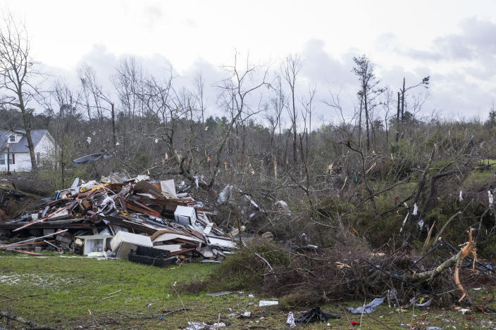 Fallen trees cover the ground by weather-damaged properties in Clanton, Ala., the morning following a large outbreak of severe storms across the southeast, Thursday, March 18, 2021. Possible tornadoes knocked down trees, toppled power lines and damaged homes in multiple locations across the state of Alabama. (AP Photo/Vasha Hunt)