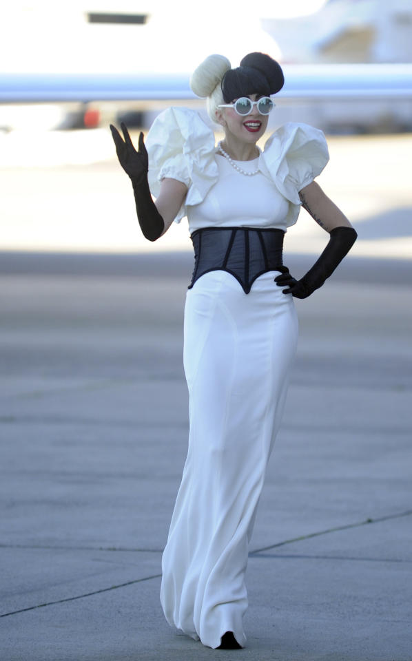 Performer Lady Gaga waves as she walks across the tarmac upon arrival by her private jet at Sydney airport in Sydney, Australia, Saturday, July 9, 2011. Lady Gaga is in Sydney for a one-off show at Sydney's Town Hall. (AP Photo/Dean Lewins, Pool)