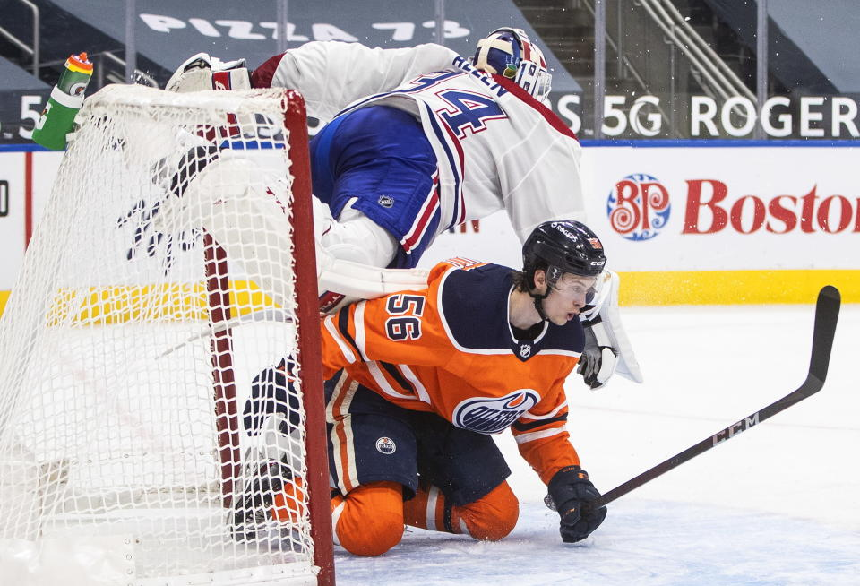 Edmonton Oilers' Kailer Yamamoto (56) crashes into Montreal Canadiens goalie Jake Allen (34) during second-period NHL hockey game action in Edmonton, Alberta, Monday, Jan. 18, 2021. (Jason Franson/The Canadian Press via AP)
