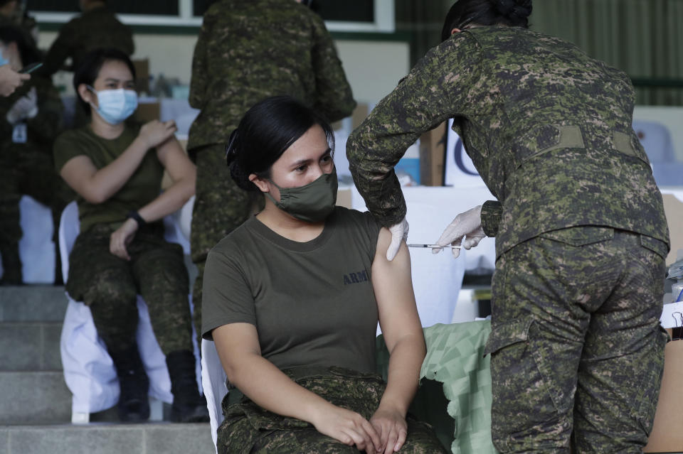 Philippine Army women soldiers are injected with the Sinovac vaccine from China during a vaccination at Fort Bonifacio, Metro Manila, Philippines on Tuesday, March 2, 2021. The Philippines launched a vaccination campaign to contain one of Southeast Asia's worst coronavirus outbreaks but faces supply problems and public resistance, which it hopes to ease by inoculating top officials. (AP Photo/Aaron Favila)