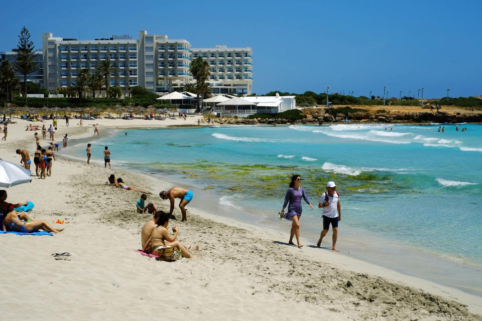Tourist and local vacationed enjoy the popular Nissi Beach in southeast resort of Ayia Napa, in the eastern Mediterranean island of Cyprus, Saturday, May 22, 2021. Cypriot hotel and other tourism-related business owners say they'd like to see the COVID-19 pandemic-induced uncertainty over travel bookings to the tourism-reliant island nation winding down by July when they're hoping authorities in Cyprus' main markets including the U.K., Russia, Germany and the Scandinavian countries will make it easier for their citizens to travel abroad. (AP Photo/Petros Karadjias)