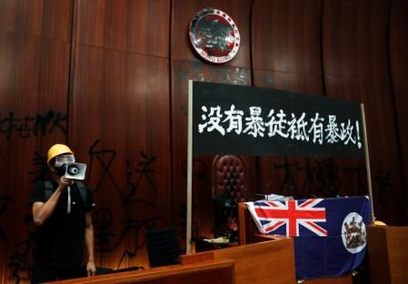 A man uses a loudspeaker as he stands next to a colonial flag of Hong Kong and a banner displayed inside a chamber, after protesters broke into the Legislative Council building during the anniversary of Hong Kong's handover to China in Hong Kong