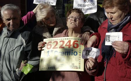 "Pensioners, who won part of the first prize of Spain's Christmas Lottery ""El Gordo"" (The Fat One), celebrate outside a lottery shop where the lottery number was sold in Leganes, near Madrid, December 22, 2013. REUTERS/Andrea Comas"