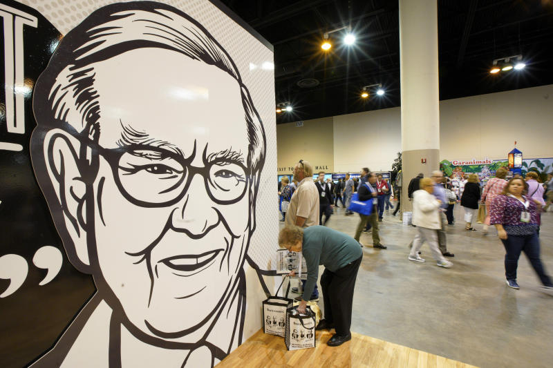 A Berkshire Hathaway shareholder arranges her shopping next to a large drawing of Chairman and CEO Warren Buffett, during a shareholders shopping event in Omaha, Neb., Friday, May 3, 2019, one day before Berkshire Hathaway's annual shareholders meeting. An estimated 40,000 people are expected in town for the event, where Chairman and CEO Warren Buffett and Vice Chairman Charlie Munger will preside over the meeting and spend hours answering questions. (AP Photo/Nati Harnik)