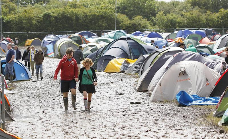 Festival goers walk through the mud at the campsite at the Isle of Wight festival on the Isle of Wight england Friday June 22, 2012.  Hundreds of music fans have been stranded in their cars overnight after rainstorms caused chaos on travel routes to the Isle of Wight Festival.  (AP Photo/Peter Byrne/PA) UNITED KINGDOM OUT