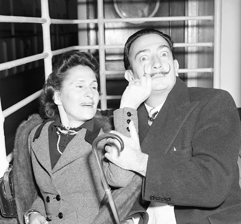 (Original Caption) 12/24/51-New York: Salvador Dali, surrealist painter, and his wife, Gala, arrive in New York, Dec. 24, aboard the Liner America. Dali, whose newly-regrown handlebars mustache is twirled by his playful spouse, returned to the U.S. after eight months abroad. The whimsical artist has had exhibitions in France, England and Spain.