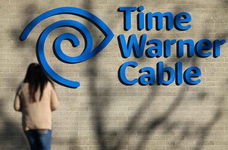 A woman walks in front of the Time Warner Cable logo at its office in San Diego