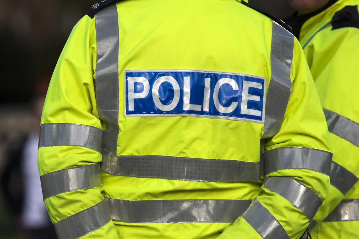 Shot of the back of a police officer's jacket with the word police written across the back
