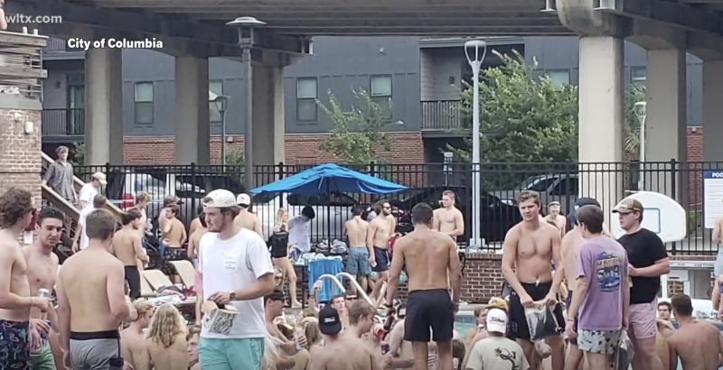 Pictured are dozens of people at a pool party in South Carolina ignoring social distancing rules.