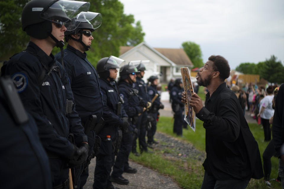 A demonstrator holding a sign jumps up and down so police officers behind the front lines could see it, outside the Oakdale, Minn,, home of fired Minneapolis police Officer Derek Chauvin on Wednesday evening, May 27, 2020. The mayor of Minneapolis called Wednesday for criminal charges against the white police officer seen on video kneeling against the neck of Floyd George, a handcuffed black man who complained that he could not breathe and died in police custody. (Jeff Wheeler/Star Tribune via AP)