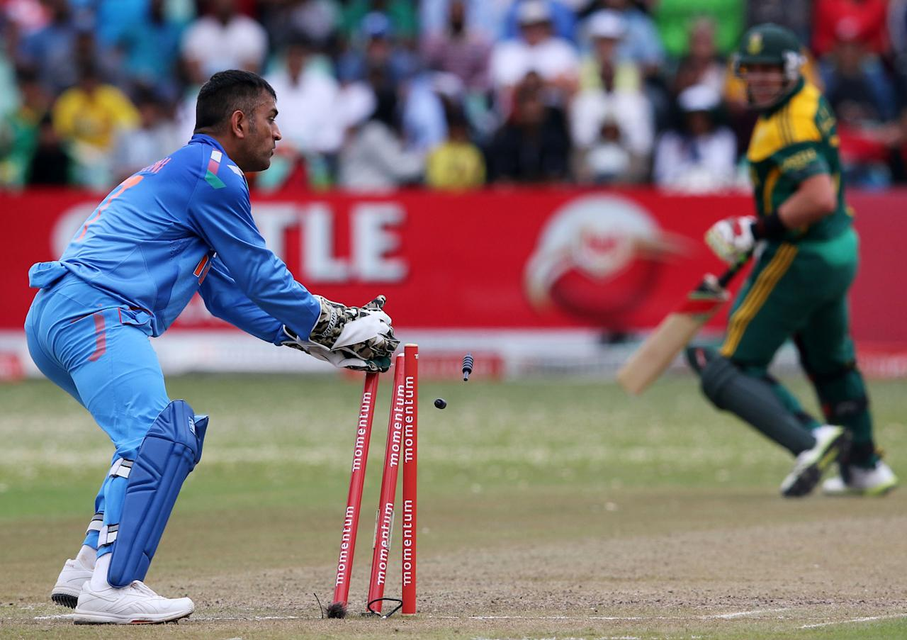 India's MS Dhoni (L) runs out South Africa's JP Duminy during the One day International (ODI) cricket match between India and South Africa at SAHARA Stadium Kingsmead in Durban on December 8, 2013.   AFP PHOTO / ANESH DEBIKY