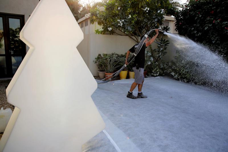 In this Saturday, Dec. 21, 2013 photo, Ben Elliott-Scott of Desert Snow company, a company which specializes in artificial snow, blasts trees with manmade flurries to turn them wintery white, a few hours ahead of a Christmas party at a private villa, in Dubai, United Arab Emirates. The Middle East's brashest city is increasingly embracing the trappings of Christmas in a way that would be unthinkable in more conservative parts of the Muslim world. Christmas trees adorn shopping centers and residential neighborhoods, and high-end hotels try to outdo one another with extravagant and boozy holiday dinners. (AP Photo/Kamran Jebreili)