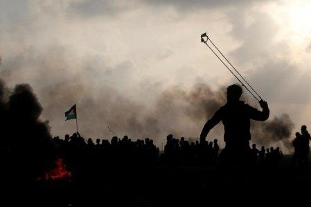 A Palestinian demonstrator uses a sling to hurl stones towards Israeli troops during clashes, near the border with Israel in the east of Gaza City January 12, 2018. REUTERS/Mohammed Salem