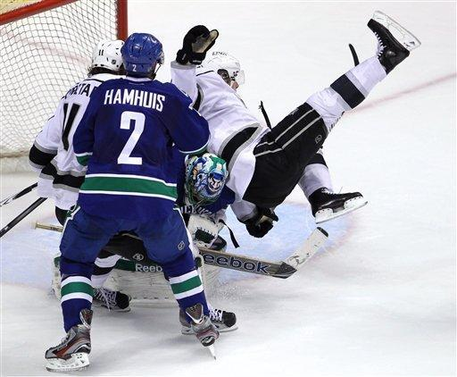Los Angeles Kings center Anze Kopitar (11) and Vancouver Canucks defenseman Dan Hamhuis (2) watch as Kings right wing Dustin Brown (23) crashes on top of Canucks goalie Roberto Luongo (1) during the second period of Game 2 of a first-round NHL hockey Stanley Cup playoff series in Vancouver, British Columbia, Friday, April, 13, 2012. (AP Photo/The Canadian Press, Jonathan Hayward)