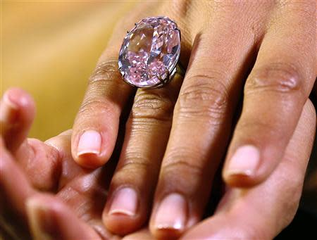 A model displays the 'Pink Star' 59.60 carat oval cut pink diamond at Sotheby's in Geneva