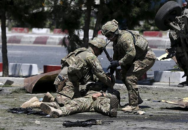 <p>U.S. soldiers attend to a wounded soldier at the site of a blast in Kabul, Afghanistan June 30, 2015. At least 17 people were wounded in a suicide bomb attack on NATO troops as their truck convoy passed down the main road running between Kabul's airport and the U.S. embassy, police and health ministry officials said. (Photo: Omar Sobhani/Reuters) </p>