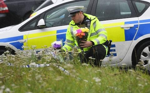 A police officer lays flowers at the scene where Pc Harper was murdered in Berkshire - Credit: Rex