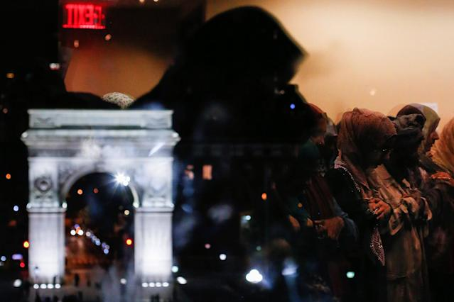 <p>Washington Square Arch is seen on the left as Muslim women praying Tarawih prayers are reflected in the window of the Islamic Center at New York University ahead of Ramadan in Manhattan, New York, May 26, 2017. (Gabriela Bhaskar/Reuters) </p>