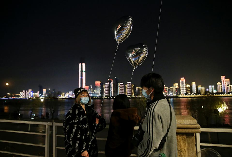 People wearing masks hold balloons by a river on New Year's Eve in Wuhan. (Reuters)