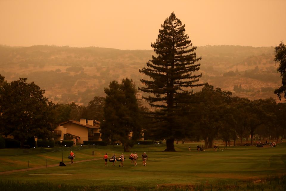 Golfers warm up on the driving range on Wednesday morning under rust-colored skies. (Photo by Jed Jacobsohn/Getty Images)