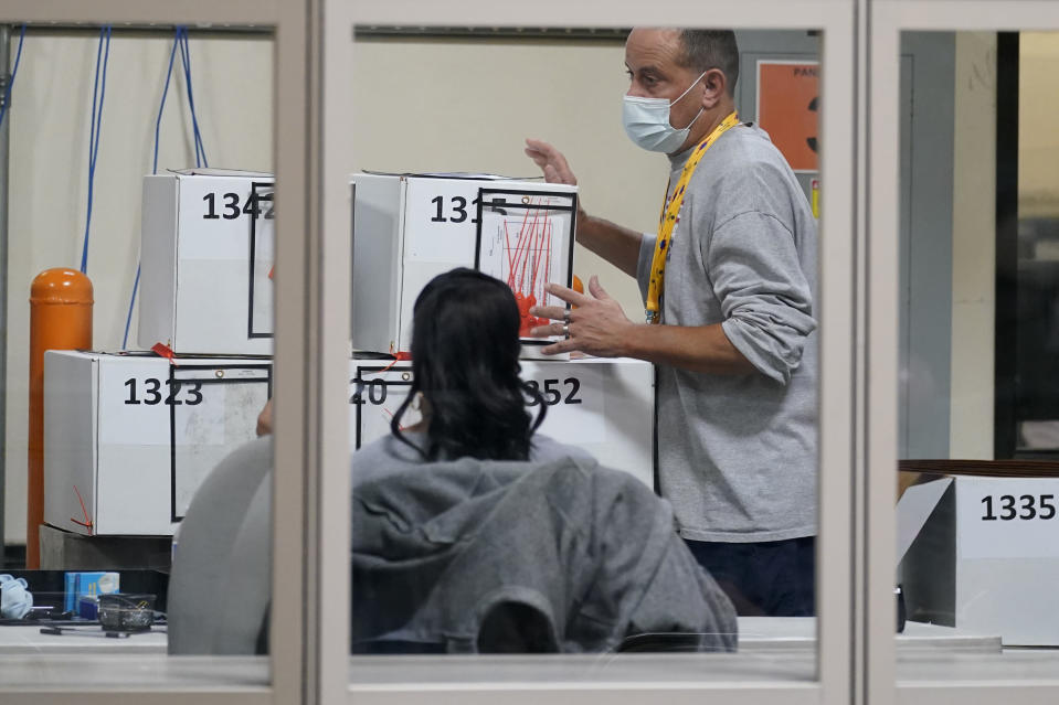 FILE - In this Nov. 5, 2020 file photo, a county election worker moves boxes of mail-in ballots at a tabulating area at the Clark County Election Department in Las Vegas. County officials in Nevada began signing off Monday, Nov. 16 on results of the Nov. 3 election that gave Democratic candidate Joe Biden a 33,596-vote statewide victory over Republican Donald Trump in the presidential contest. The former vice president drew a little over 50% of the vote and Trump a little under 48% in unofficial results submitted for approval by commissioners in counties including Washoe, surrounding Reno, and Clark, which encompasses Las Vegas. (AP Photo/John Locher, File)