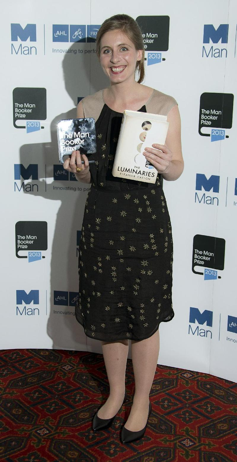 New Zealand author Eleanor Catton poses after being announced the winner of the Man Booker Prize for Fiction, holding her prize and her book for the photographers, in central London, Tuesday Oct. 15, 2013. Catton won the 50,000 pounds ($80,000) prize with her book 'The Luminaries'. (Photo by Joel Ryan/Invision/AP)