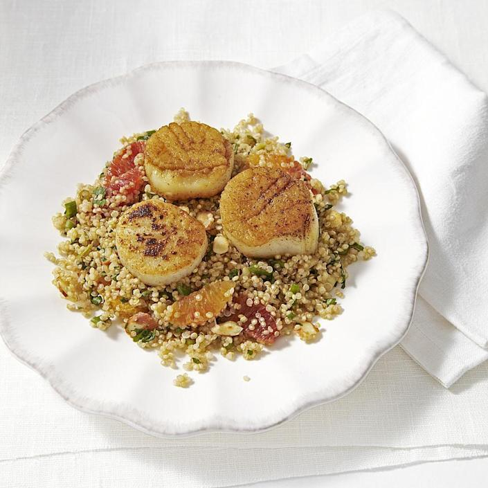 """<p>Make whole grains the center of your dinner plate with this citrus-studded quinoa pilaf recipe topped with sweet seared sea scallops. Be sure to buy """"dry"""" sea scallops (scallops that have not been treated with sodium tripolyphosphate, or STP). Scallops treated with STP (""""wet"""" scallops) are higher in sodium, have a mushy texture and do not brown properly.</p>"""