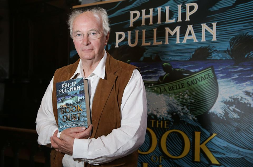 "British author Philip Pullman poses with his new book 'La Belle Sauvage: The Book of Dust Volume One' during a photo call at Convocation House, Bodleian Libraries, in Oxford, southern England, on October 18, 2017. The 17-year wait for a return to the mystical world of British author Philip Pullman's ""Dark Materials"" series will end on October 19 with the release of ""La Belle Sauvage"", the first volume of a new trilogy. / AFP PHOTO / Daniel LEAL-OLIVAS        (Photo credit should read DANIEL LEAL-OLIVAS/AFP/Getty Images)"