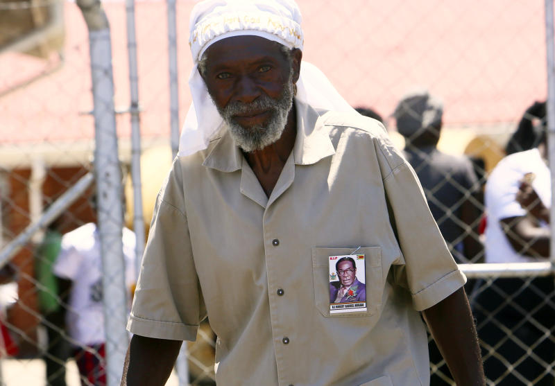 A supporter of former Zimbabwean President Robert Mugabe is seen near the entrance to his rural home in Zvimba, about 100 kilometer north west of the capital Harare, Saturday, Sept. 28, 2019. According to a family spokesperson Mugabe is expected to be buried at the residence after weeks of drama mystery and contention over his burial place.(AP Photo/Tsvangirayi Mukwazhi)