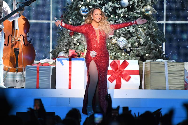 Mariah Carey stands on stage with her arms stretched out holding a microp