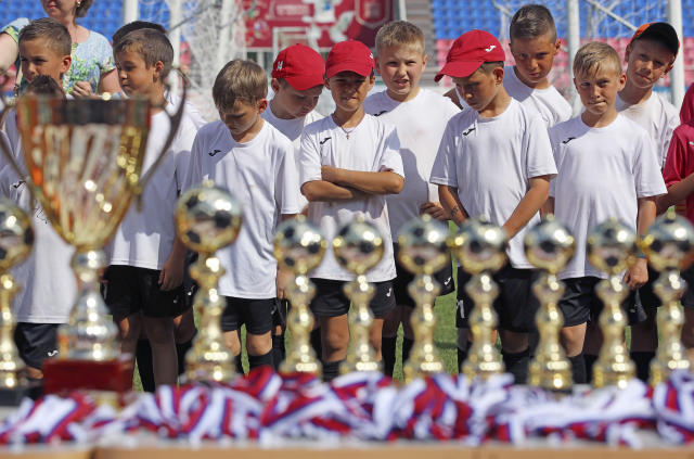 In this photo taken on Thursday, May 17, 2018, boys stand next to trophies during a children soccer tournament at the Start Stadium in Saransk, Russia. The Start Stadium in Saransk may not look like much, but its the jumping-off point for hundreds of young Russians dreams of soccer stardom. (AP Photo)